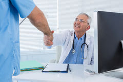 Doctor and surgeon shaking hands royalty free stock image