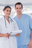 Doctor and surgeon smiling at the camera Royalty Free Stock Photos