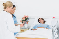 Doctor and surgeon visiting female patient Stock Photos