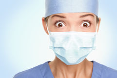 Doctor surgeon woman shocked. Doctor / surgeon shocked - funny. Woman closeup portrait of young doctor, surgeon or nurse surprised starring with big eyes wearing Royalty Free Stock Images