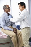 Doctor In Surgery Listening To Male Patient's Chest Stock Photography