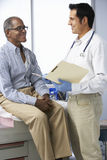 Doctor In Surgery With Male Patient Reading Notes Royalty Free Stock Photos