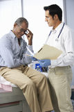 Doctor In Surgery With Male Patient Reading Notes Royalty Free Stock Images