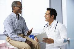 Doctor In Surgery With Male Patient Using Digital Tablet Stock Photography