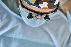 Surgeon in operating room. Doctor during the surgery in the operation room. He wears a blue mask, colorful hat and glasses. His assistant is next to him. Closeup Royalty Free Stock Images
