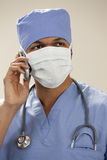Doctor in surgical mask on the phone Royalty Free Stock Photography