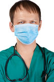 Doctor with surgical mask and stethoscope. Close-up portrait of a handsome young doctor in surgical mask and stethoscope, isolated on white background Royalty Free Stock Photography