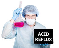 Doctor in surgical uniform, holding flask and digital tablet pc with acid reflux sign. technology, internet and Stock Photography