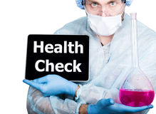 Doctor in surgical uniform, holding pink flask and digital tablet pc with health check sign. internet technology and Royalty Free Stock Image
