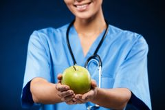 Doctor swith stethoscope holding and showing green apple