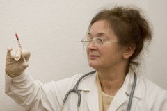 Doctor with syringe. An older doctor woman holds syringe in her hand stock images