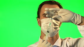 Doctor with syringe drawing up clear liquid form bottle stock video footage
