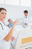 Doctor with a syringe. In front of hospitalized women and doctor Royalty Free Stock Photo