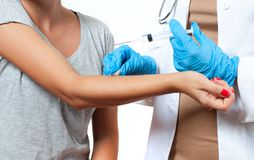 Vaccination. Doctor injecting flu vaccine to patient`s arm. Doctor with syringe making vaccination to patient.  Doctor making women an injection Royalty Free Stock Photo