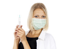 Doctor with a syringe and a mask Stock Image