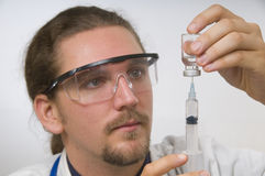 Doctor with syringe and vial Stock Photo