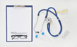 Doctor table with medicines, stethoscope and glasses, top view Stock Photos