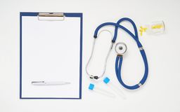 Doctor table with medicines, stethoscope, clipboard and pen, top view Royalty Free Stock Images