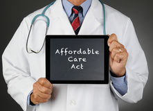 Doctor Tablet Computer Affordable Care Act. Closeup of a doctor holding a tablet computer with a chalkboard screen with the words Affordable Care Act (Obamacare Stock Image