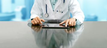Doctor with tablet computer at hospital office. Male doctor sitting at table with tablet computer in hospital office. Medical healthcare staff and doctor service stock photo