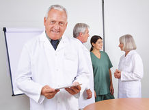 Doctor with tablet computer and team stock photo