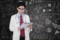Doctor with tablet in front of blackboard. Young male doctor using a tablet computer while standing in front of blackboard Stock Images