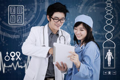 Doctor with tablet and futuristic interface background. Male doctor with his partner using a digital tablet in front of the futuristic interface background Royalty Free Stock Image