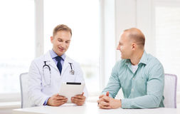 Doctor with tablet pc and patient in hospital Stock Photos