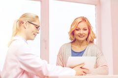 Doctor with tablet pc and woman at hospital Royalty Free Stock Photos