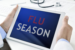 Doctor and tablet with the text flu season Stock Photos