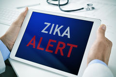 Doctor with a tablet with the text zika alert. Closeup of a doctor man sitting at his office desk holding a tablet computer with the text zika alert in its royalty free stock image