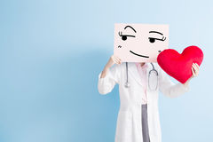 Doctor take look somewhere billboard. Woman doctor take look somewhere billboard and heart isolated on blue backgorund, asian royalty free stock photos