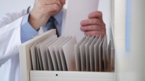 Doctor take a medical document from archive and write information.  stock video footage