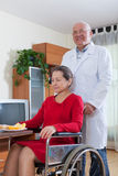 Doctor takes care of   woman in   wheelchair. Stock Images