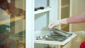 Doctor takes out a tray of medical instruments out of the shelf. stock video footage