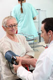 Doctor taking blood pressure Royalty Free Stock Images