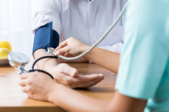 Doctor taking blood pressure. Close up of patient and doctor taking blood pressure Royalty Free Stock Photos