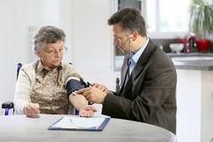 Doctor taking blood pressure of an elderly lady Stock Photos