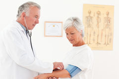 Doctor taking the blood pressure of his patient Stock Photos