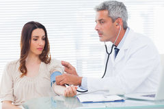 Doctor taking blood pressure of his patient Royalty Free Stock Photos