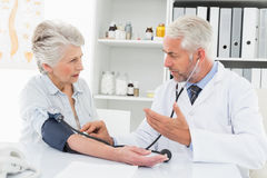 Doctor taking the blood pressure of his retired patient Stock Image