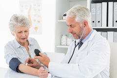 Doctor taking the blood pressure of his retired patient Royalty Free Stock Image