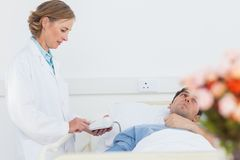Doctor taking the blood pressure of male patient Stock Photos