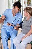 Doctor taking the Blood Pressure Royalty Free Stock Photos