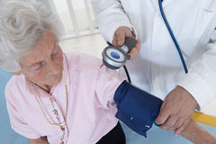 Doctor taking the blood pressure Royalty Free Stock Images