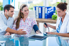 Doctor taking the blood pressure of a pregnant patient with her husband. In an examination room Stock Photography