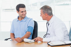 Doctor taking blood pressure of smiling patient. In bright surgery Royalty Free Stock Photo