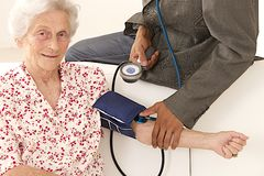 Doctor taking blood pressure to patient at home Royalty Free Stock Photography