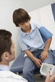Doctor taking boy's blood pressure. Closeup of a male doctor taking boy's blood pressure Royalty Free Stock Images