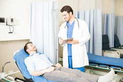 Doctor taking care of patient in hospital. Handsome male doctor with a clipboard standing next to a bed and talking with patient Stock Photo